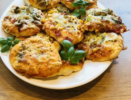 Gebackene Pizzabrötchen auf Teller mit Basilikum dekoriert.